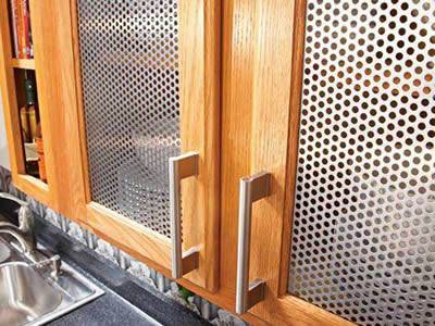 Cabinet screen with metal handles is made of perforated metal mesh.